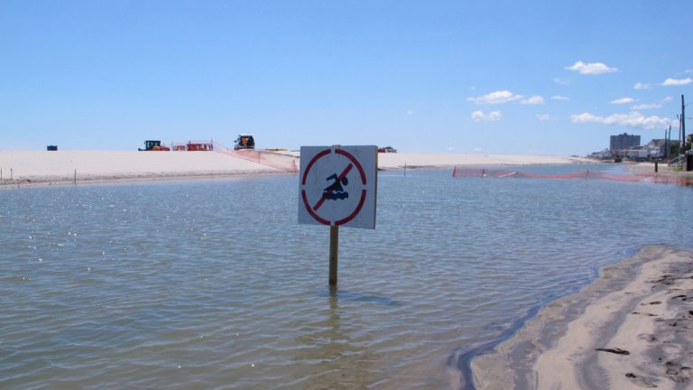 This July 31, 2017 photo shows a no swimming sign in one of numerous large pools of water that have formed on the beach in Margate N.J. due to heavy rains. The water is blocked from draining into the ocean by new sand dunes being built as part of a storm protection program that Margate residents vigorously fought, claiming that the dunes would cause exactly the type of standing water that has occurred. (Wayne Parry/AP Photo)