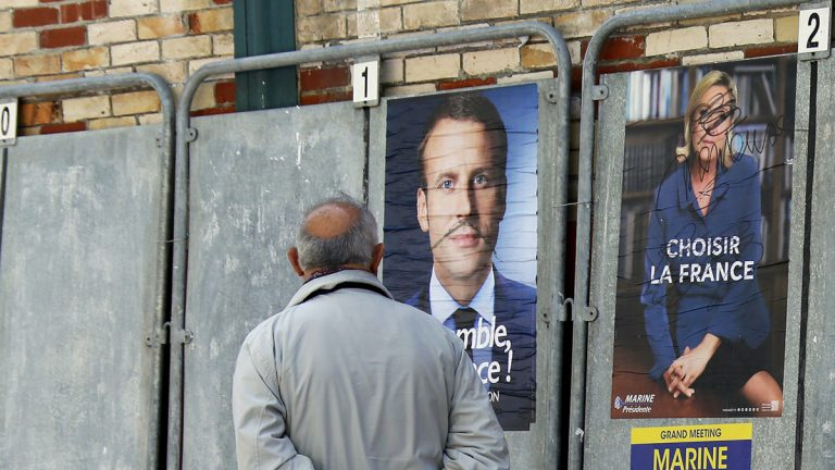 A man walks past defaced election campaign posters for French centrist presidential candidate Emmanuel Macron and far-right candidate Marine Le Pen, in Saint Jean de Luz, southwestern France, Thursday, May 4, 2017. France vote Sunday May 7 for the second round of the presidential election. (Bob Edme/AP Photo)