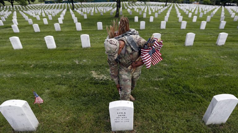 U.S. Army Staff Sgt. Anthony Ellis with the 3d U.S. Infantry Regiment (The Old Guard), places a flag at a headstone for