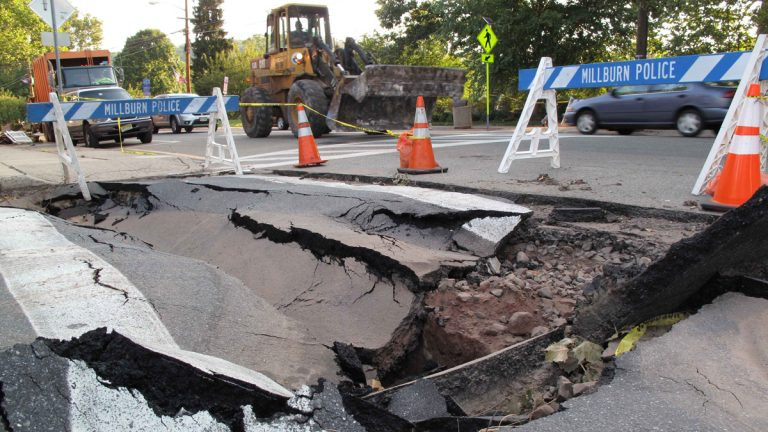 In this Sept. 2, 2011 photo, a front loader passes a sink hole in a Millburn, N.J. intersection. (Chris Hawley/AP Photo)