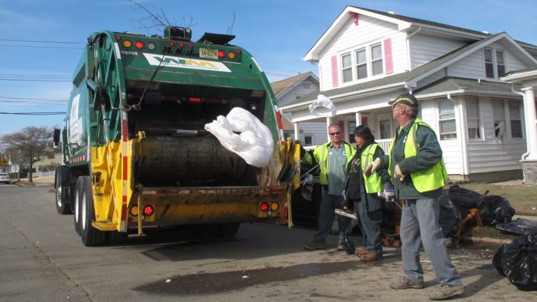 This file photo shows public works employees tossing waterlogged bedding into a garbage truck in Point Pleasant Beach N.J. (Wayne Parry/AP Photo)