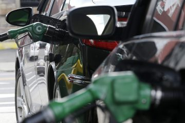 Nozzles pump gas into vehicles at a BP gas station. (Julio Cortez/AP Photo)