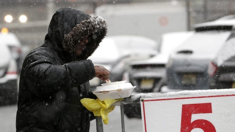 Snow falls over a homeless person while eating a pre-Thanksgiving meal from the St. John's Church soup kitchen