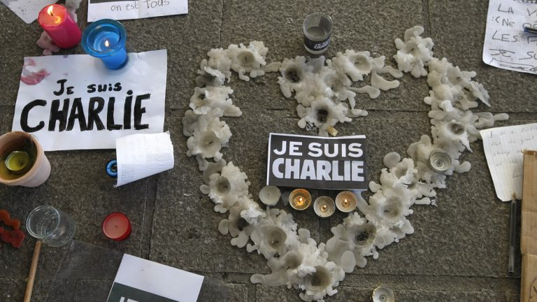 A heart formed by melted candles is on the ground of the Old-Port to pay tribute to the victims of the satirical newspaper 'Charlie-Hebdo,' in Marseille, southern France, Thursday, Jan. 8, 2015, a day after masked gunmen stormed the offices of a satirical newspaper and killed 12 people. French police hunted Thursday for two heavily armed men — one with a terrorism conviction and a history in jihadi networks — in the methodical killing of 12 people at a satirical newspaper that caricatured the Prophet Muhammad. (Claude Paris/AP Photo)