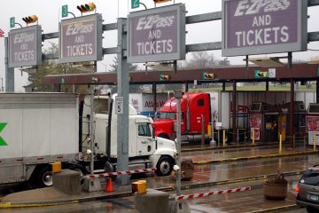 Trucks and cars move through a Pennsylvania Turnpike toll plaza in Carlisle, Pa