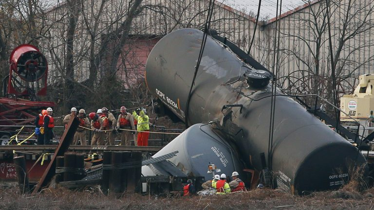 Workers secure lines around a train tank car as they prepare to pull it up with a crane from a crash site on a small bridge on the Mantua Creek