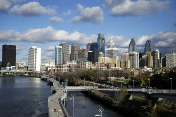 Clouds pass over the Schuylkill River and Philadelphia's skyline. Officials are considering a new plan to preserve or build 100,000 housing units over the next 10 years. (Matt Rourke/AP Photo)