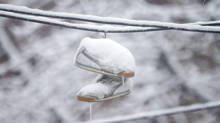 Snow covered shoes dangle from utility lines Thursday, March 5, 2015, during a winter storm in Philadelphia. The Philadelphia area was forecast to receive 5 to 8 inches of snow through Thursday, with lesser amounts to the north and more to the south. (Matt Rourke/AP Photo)