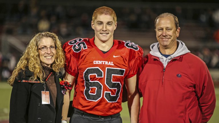 This Oct. 31, 2014, photo shows Timothy Piazza, (center), with his parents Evelyn and James Piazza, during Hunterdon Central Regional High School football's 'Senior Night' at the high school's stadium in Flemington, N.J. (Patrick Carns via AP)