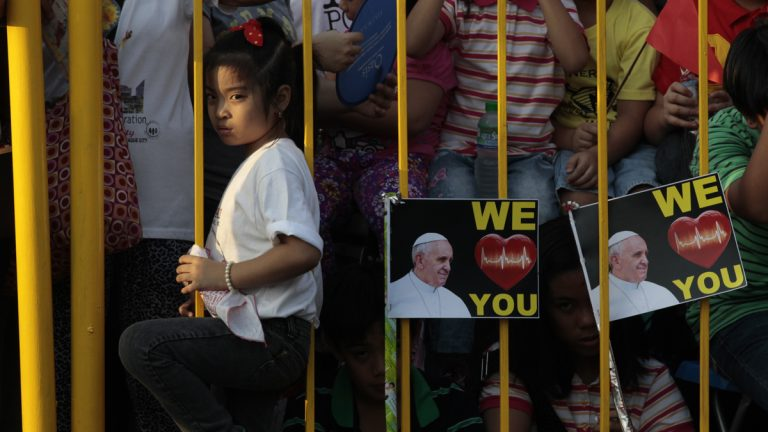 A young girl waits behind a fence for hours for the arrival of Pope Francis in Manila, Philippines, Thursday, Jan. 15, 2015. (Wally Santana/AP Photo)