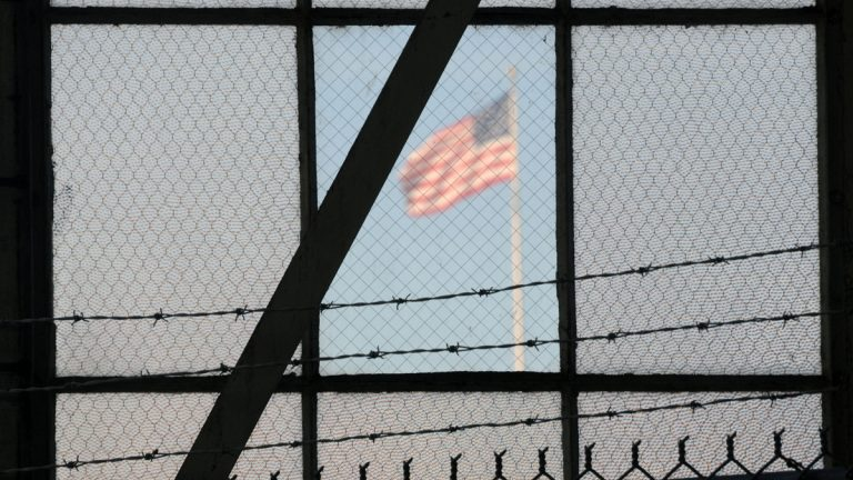 In this photo reviewed by the U.S. Department of Defense, a U.S. flag waves above the the Camp Justice compound at Guantanamo Bay U.S. Naval Base, Cuba, Wednesday, Oct. 17, 2012. (AP Photo/Toronto Star, Michelle Shephard, Pool)
