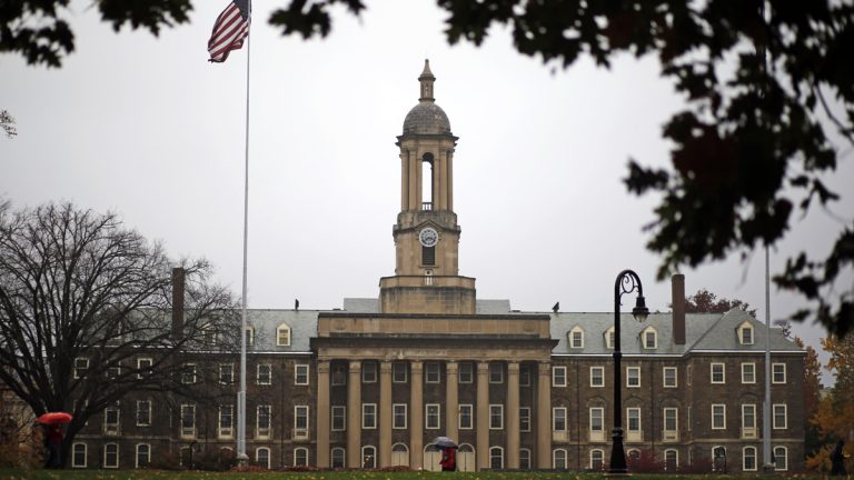 A Penn State student walks in the rain past Old Main on the Penn State main campus in State College, Pa., Wednesday, Oct. 28, 2015. (Gene J. Puskar/AP Photo)