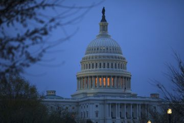 The capitol is seen against a darkened blue sky