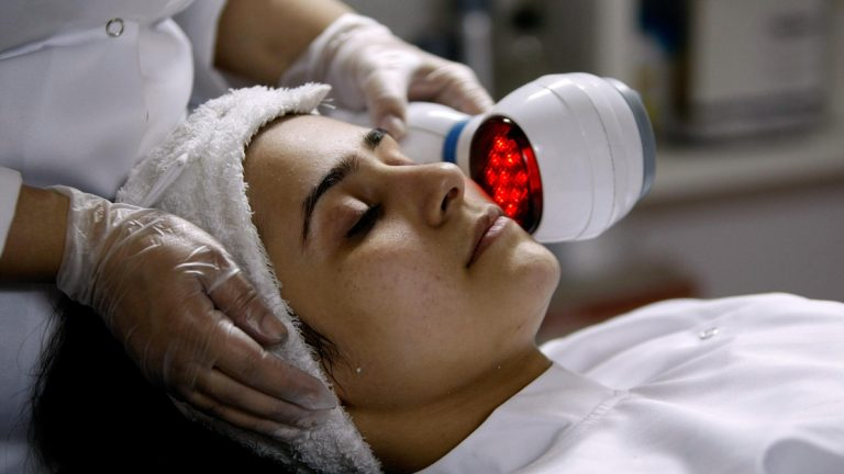 A doctor uses a machine to heat up the skin of a patient receiving treatment to lighten her skin (Hassan Ammar/AP Photo)
