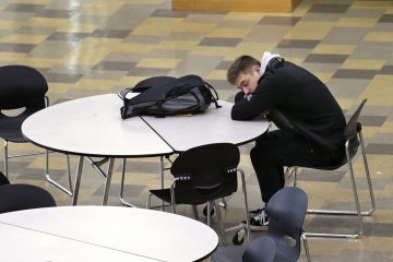 In this photo taken Nov. 23, 2015, a student leans on a table in the cafeteria during first period at Roosevelt High School in Seattle. More school districts around the U.S. are heeding the advice of scientists who have long said that pushing back school start times can improve student health or academic output. (Elaine Thompson/AP Photo)