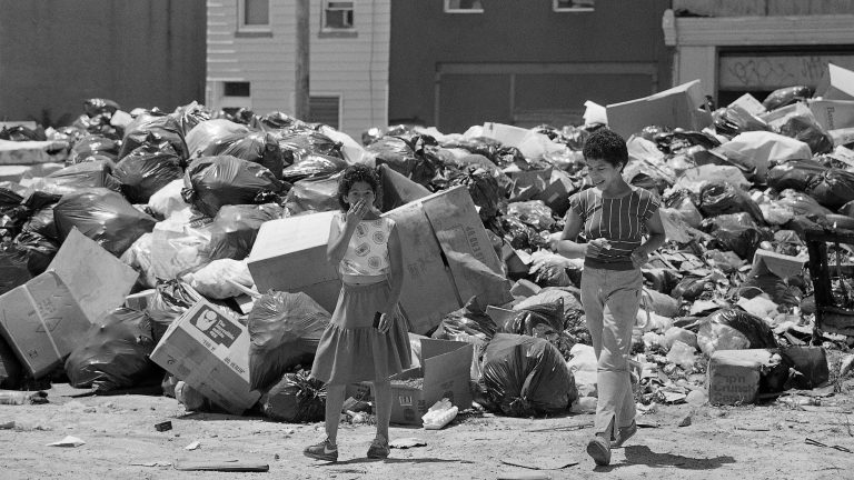 Marybel Colon, 10, of Philadelphia holds her mouth and nose while cutting through a temporary dumpsite in her neighborhood in Philadelphia, July 15, 1986, due to the strike by municipal workers. The strike is in its third week. (AP Photo/Charles Krupa)