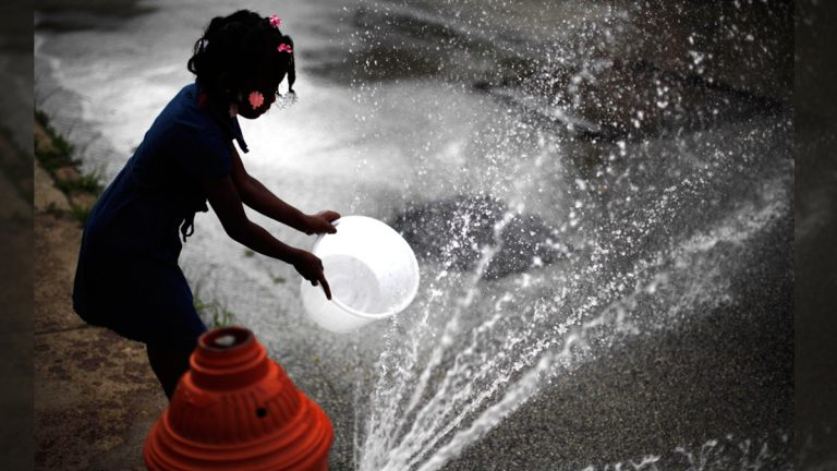 In this July 18, 2012 file photo, Jazia Pratt, 8, fills a bucket with water from a fire hydrant in the afternoon summer heat in Philadelphia. (Matt Rourke/AP Photo)