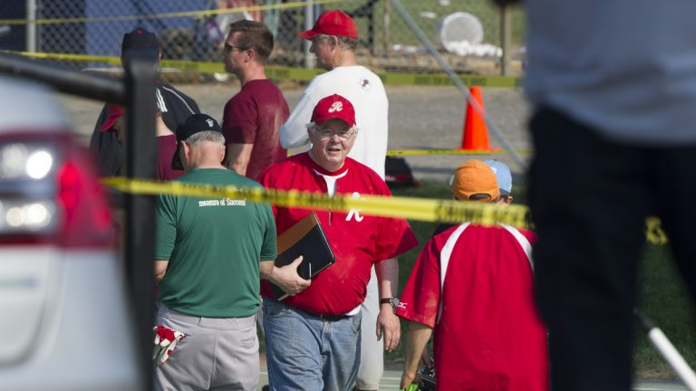 U.S. Rep. Joe Barton, R-Texas, center, and other members of the Republican congressional softball team, stand behind police tape of the scene of a multiple shooting in Alexandria, Va., Wednesday,  where House Majority Whip Steve Scalise of Louisiana was shot. (Cliff Owen/AP Photo)