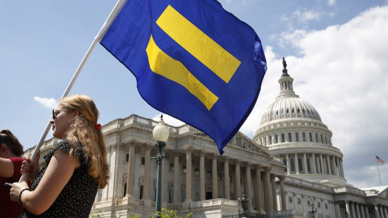 A supporter of LGBT rights holds up an 'equality flag' on Capitol Hill in Washington, Wednesday, July 26, 2017, during an event held by Rep. Joe Kennedy, D-Mass. in response to President Donald Trump's declaration that he wants transgender people barred from serving in the U.S. military 'in any capacity,' citing 'tremendous medical costs and disruption.' (Jacquelyn Martin/AP Photo)
