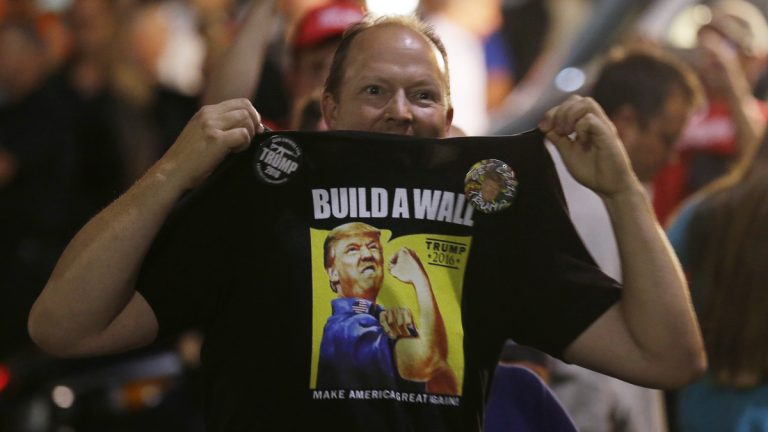 A supporter of Republican presidential candidate Donald Trump holds up his shirt, which bears the Trump slogan