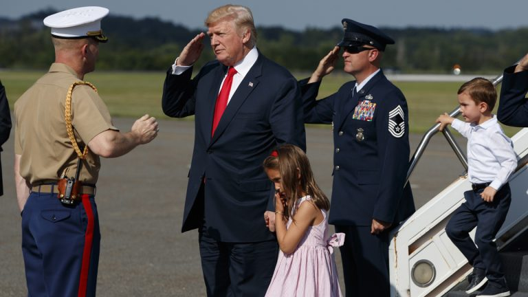 President Donald Trump salutes after walking down the steps of Air Force One with his grandchildren, Arabella and Joseph Kushner, after arriving at Morristown Municipal Airport to begin his summer vacation at his Bedminster golf club, Friday, Aug. 4, 2017, in Morristown, N.J. (Evan Vucci/AP Photo)