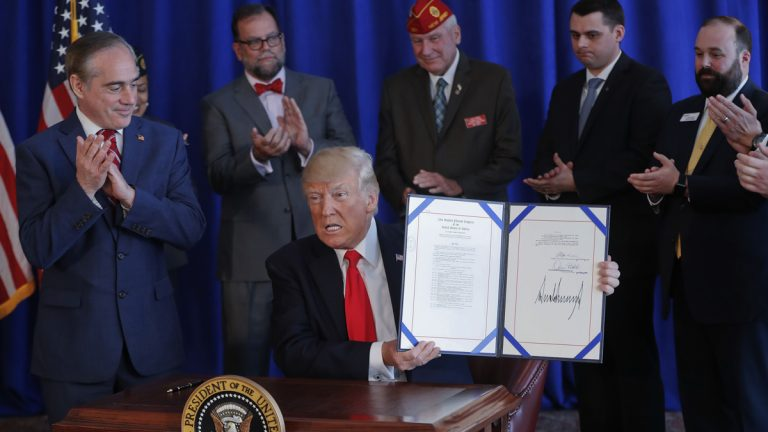 President Donald Trump holds the Veteran's Affairs Choice and Quality Employment Act of 2017 after signing it at Trump National Golf Club in Bedminister, N.J., Saturday, Aug. 12, 2017. Standing with Trump is Veterans Affairs Secretary David Shulkin, left. (Pablo Martinez Monsivais/AP Photo)