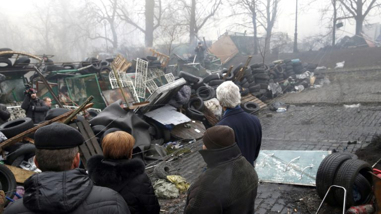 Secretary of State John Kerry looks at a barricade at the Shrine of the Fallen in Kiev