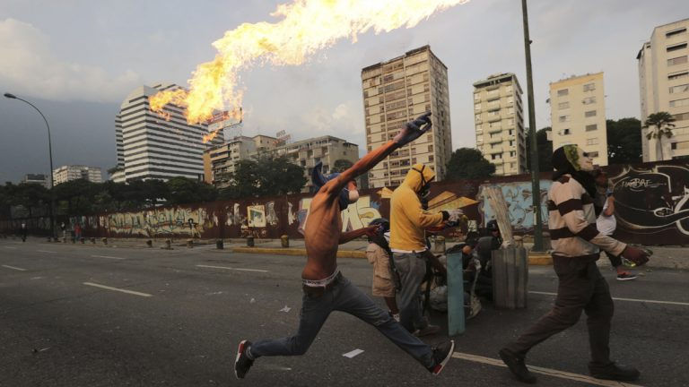 In this April 19, 2017 photo, an anti-government protesters throws a molotov bomb at security forces in Caracas, Venezuela. Tens of thousands of opponents of President Nicolas Maduro flooded the streets of Caracas in what's been dubbed the 'mother of all marches' against the embattled socialist president. (Fernando Llano/AP Photo)