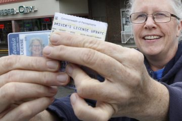 Kathryn Whitecotton covers her personal information as she shows her Pennsylvania drivers license and her address update card outside the Penndot Drivers License Center. (Keith Srakocic/AP Photo)