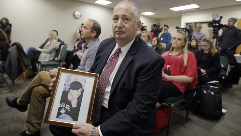 Mark Lewis, holds a photograph of his 27-year-old son who died from a heroin overdose, during a Utah Department of Health press conference where Utahns who have lost a family member to an opioid overdose as well as those who have overcome heroin and prescription opioid addictions shared their stories Wednesday, Jan. 25, 2017, in Salt Lake City. (Rick Bowmer/AP Photo)