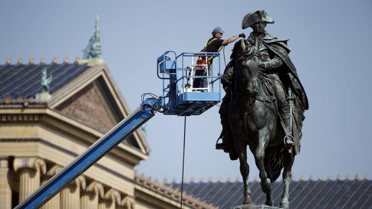 Art conservator Douglas Martenson applies a patina to a bronze statue of George Washington that stands near the Philadelphia Museum of Art. In honor of Labor Day