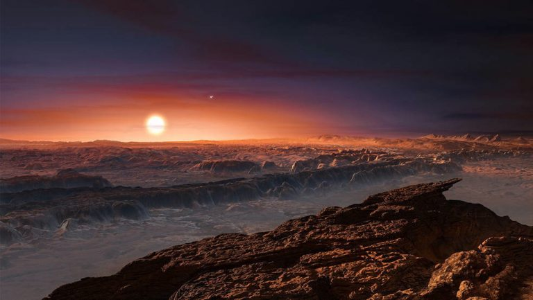This artist's impression shows a view of the surface of the planet Proxima b orbiting the red dwarf star Proxima Centauri, the closest star to the Solar System. The double star Alpha Centauri AB also appears in the image to the upper-right of Proxima itself. Proxima b is a little more massive than the Earth and orbits in the habitable zone around Proxima Centauri, where the temperature is suitable for liquid water to exist on its surface. (<a href=