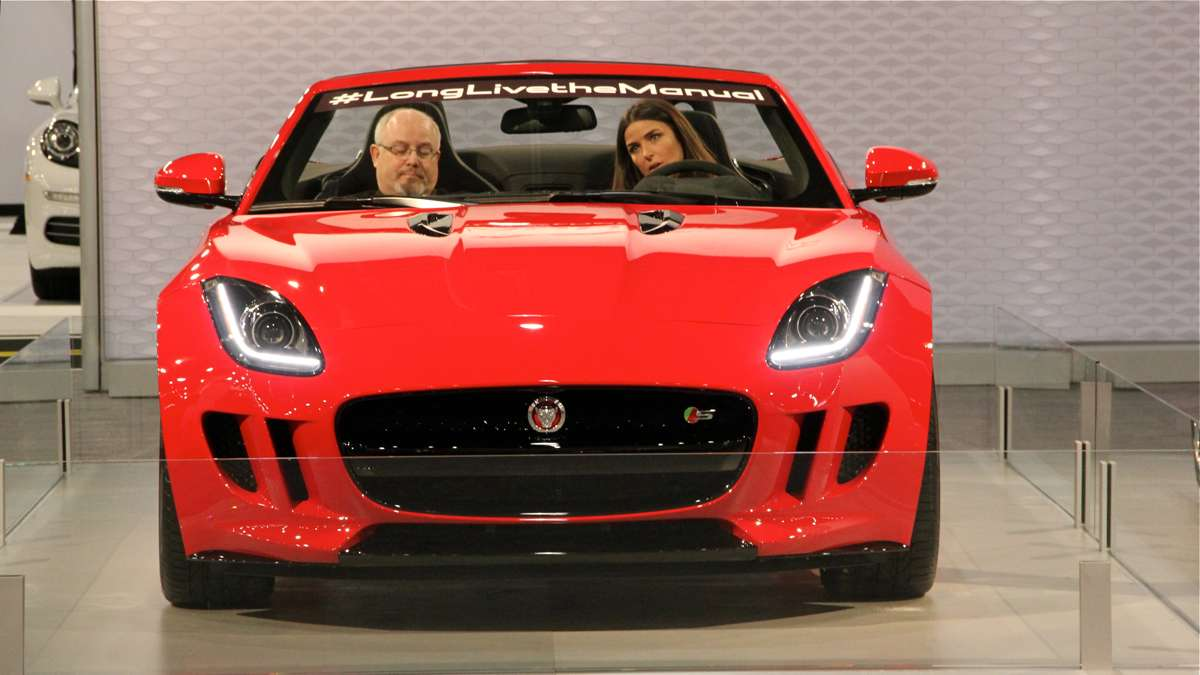 Visitors at the Philadelphia Auto Show preview try out a Jaguar. (Emma Lee/WHYY)
