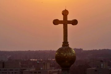 The sun sets behind the cross atop the dome of the Basilica of St. Peter and St. Paul. (AP Photo/Alex Brandon)