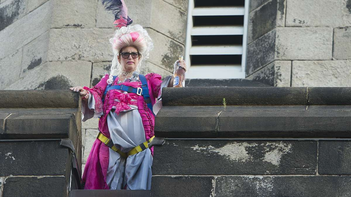 Marie Antoinette, played by Terry McNally, scowls from the top of the penitentiary walls.