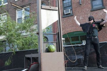 An executioner, portrayed by Eastern State Penitentiary's Sean Kelly, slices watermelons in half with a guillotine.