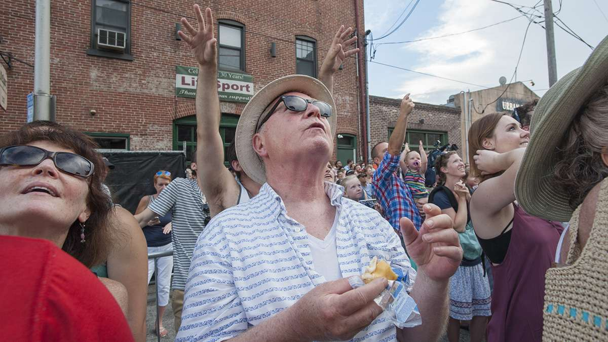 Jim Naughton of Philadelphia nibbles on a Tastykake while other members of the crowd reach skyward to catch one.