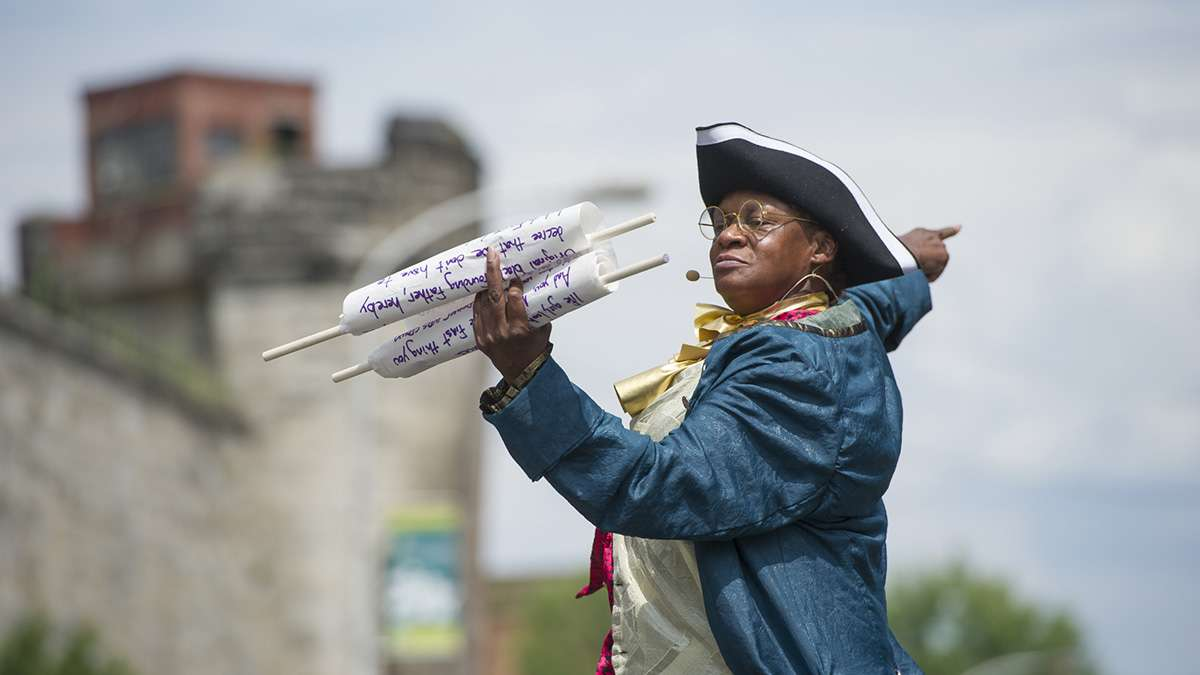Reading a proclamation opposing tyranny, Jeannie Brooks portrays Benjamin Franklin.