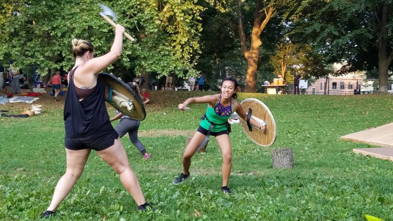 Brandi Burgess (left), playing a Volscian lieutenant, and Alexandra Palting, playing a Roman soldier, rehearse their battle scene for Shakespeare in Clark Park's production of Coriolanus. (Peter Crimmins/WHYY)