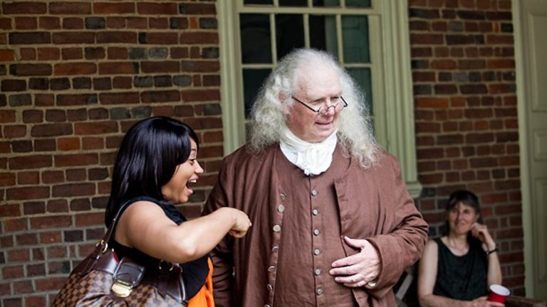 Charnice Thompson shows her excitement while getting her picture taken with Ben Franklin, as played by David Scott Taylor, on Thursday. (Brad Larrison/for NewsWorks)