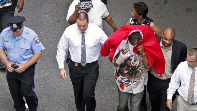 Sean Benschop, with red jacket over his head, is shown on June 8 walking with investigators as he arrives at the Philadelphia Police Department's Central Detectives Division in Center City Philadelphia. (AP Photo/ Joseph Kaczmarek)