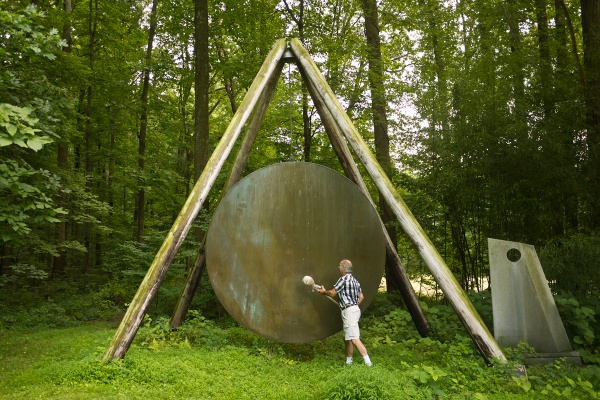 Harry Bertoia's son, Val, demonstrates one of his father's gong sound sculptures outside of his studio in Bally, Pa. (Charlie Kaier/WHYY)