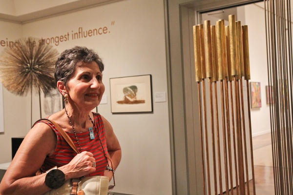 Roberta Hurley of Lambertville, N.J., fan of sculptor Harry Bertoia, appreciates the sound of one of his tonal sculptures on display at the Michener Museum. (Kimberly Paynter/WHYY)
