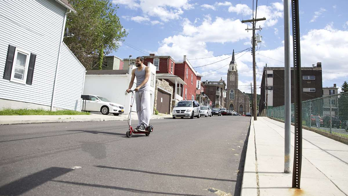 Francisco Figero, 23, rides a motorized scooter down Perry Street in South Bethlehem, Pa. (Lindsay Lazarski/WHYY)