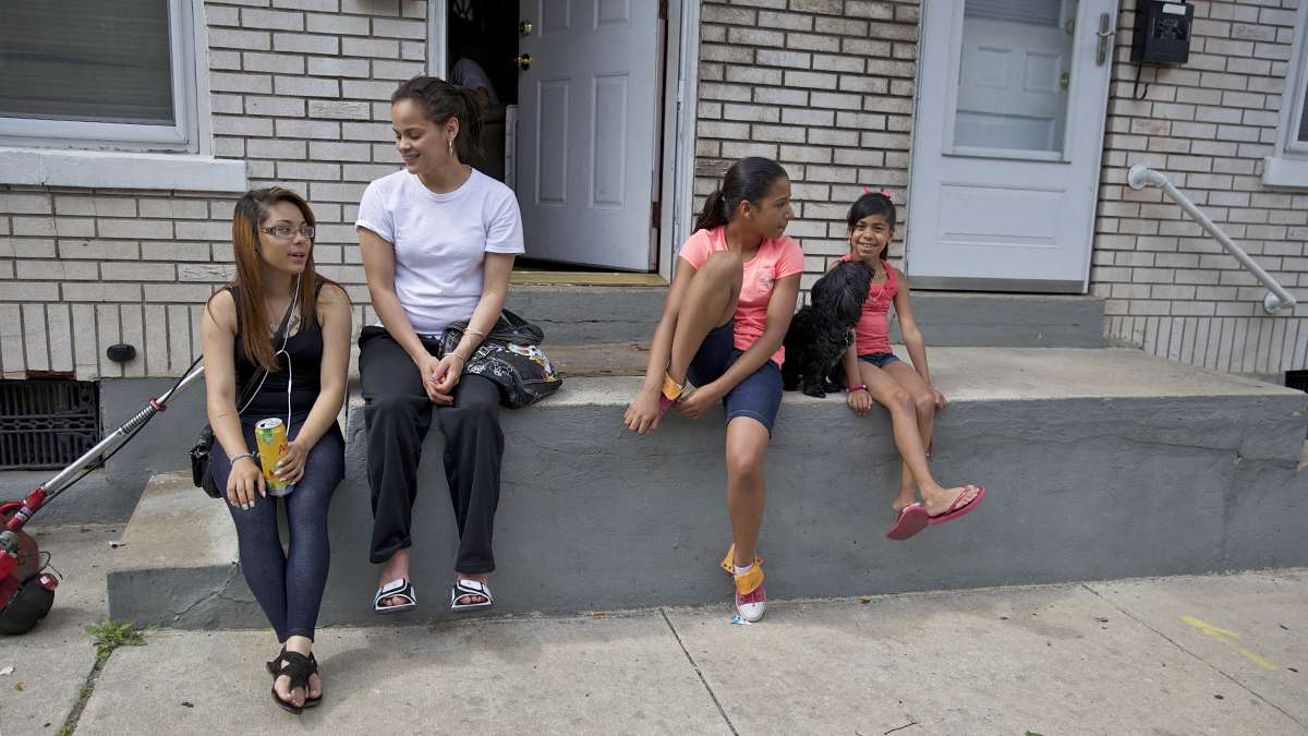Zeanna Riveria, 18, Elizabeth Alejandro, 20, Nariah Jimenez, 11, and younger sister sit on the stoop of a South Bethlehem house. (Lindsay Lazarski/WHYY)