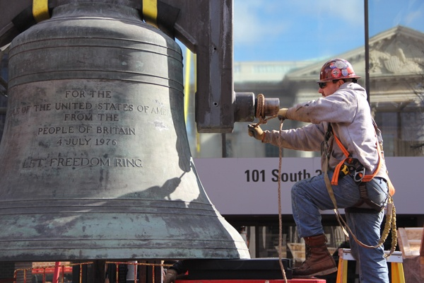 <p><p>Ironworker Michael Regan secures the Bicentennial Bell before it is lifted into a box. The bell will remain in the National Historical Park's museum storage until a new display is completed. (Emma Lee/for NewsWorks)</p></p>
