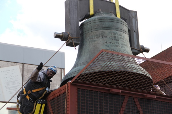 <p>Ironworker  Kevin Dukes guides the Bicentennial Bell into a crate where it will be stored until a new home is constructed for it. (Emma Lee/for NewsWorks)</p>