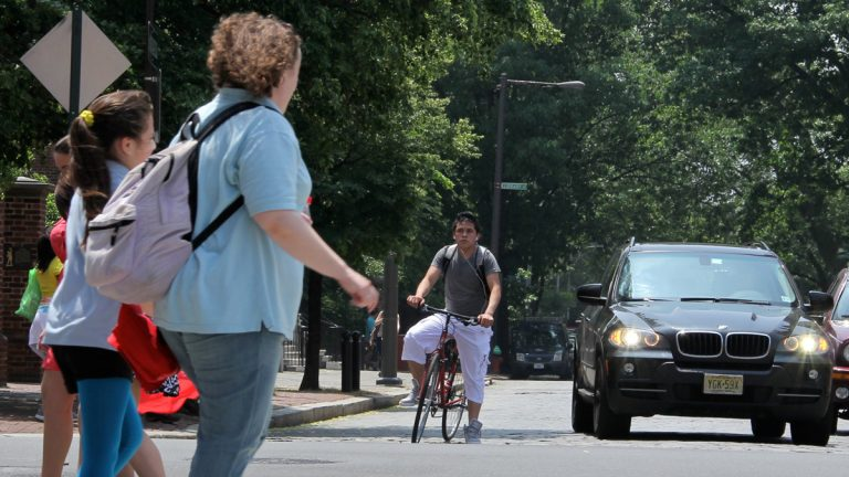 Look at everyone behaving so nicely: Bicyclist stopped at a red light, motorist peacefully coexisting, pedestrians crossing in the crosswalk. (Emma Lee/for NewsWorks)