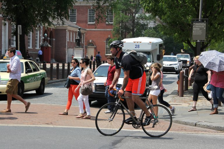 Cyclists and pedestrians cross the street in Philadelphia. (Emma Lee/Newsworks)