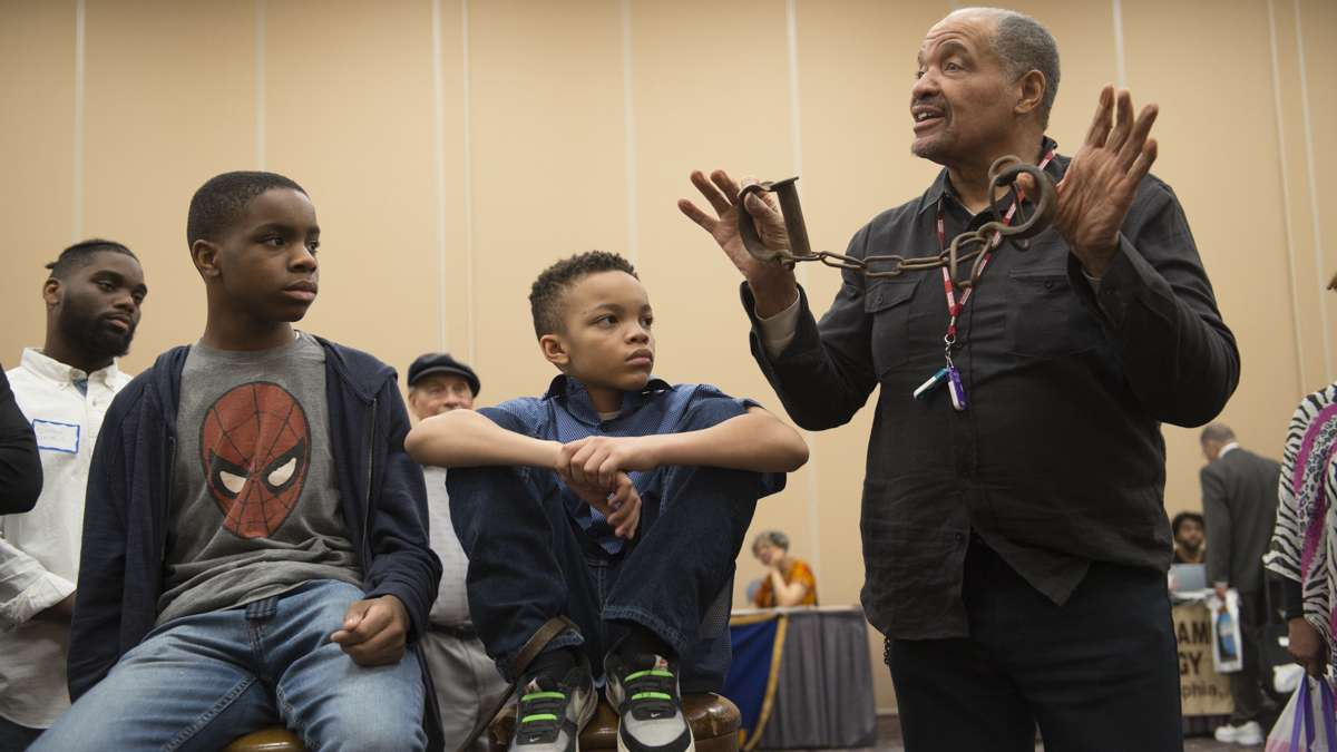 J. Justin Ragsdale holds up antique slave shackles during a demonstration on the conditions inside slave ships during the Black History and Culture Showcase in Philadelphia. (Branden Eastwood for NewsWorks)